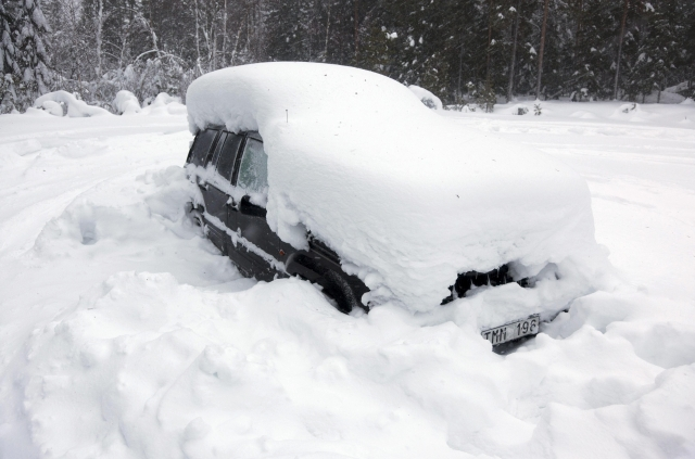 A snowed-in car is seen in the woods north of Umea